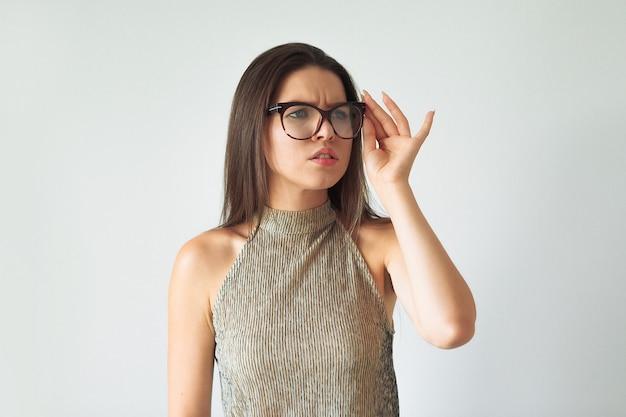 A garota surpresa espia para o lado com óculos.