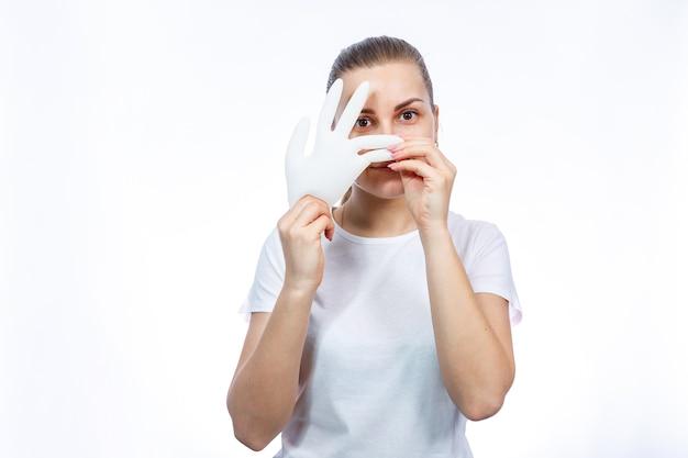 A garota tem luvas médicas brancas nas mãos. proteção contra germes e vírus. ela está com uma camiseta branca sobre um fundo branco.