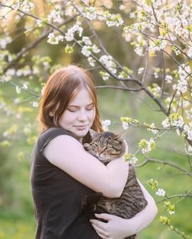 A garota tem nas mãos seu adorável gato cinza listrado ao ar livre no fundo da natureza da primavera.