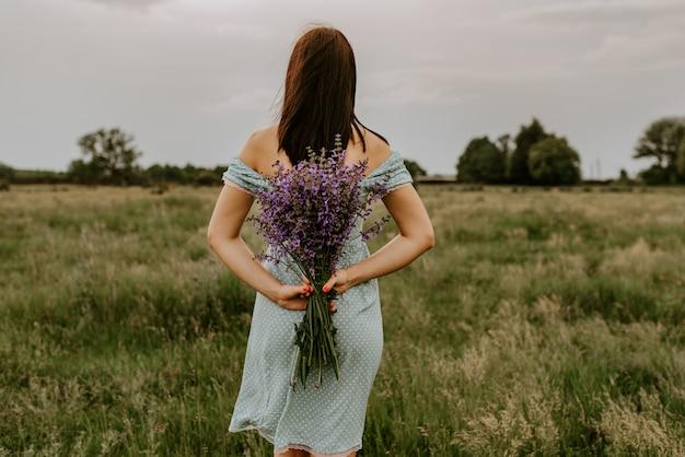 A garota tem nas mãos um buquê de flores violetas nas costas.
