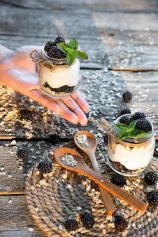 A garota tem nas mãos um frasco de vidro com iogurte fresco natural de amoras. amoras-pretas estão espalhadas sobre a mesa.
