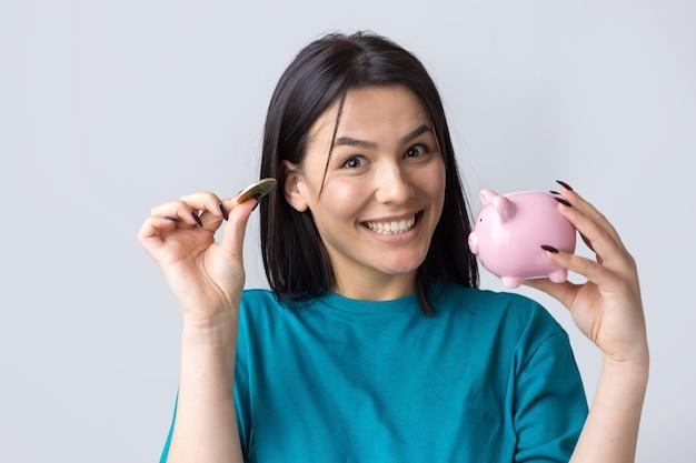A garota tem um cofrinho rosa e uma moeda nas mãos. o conceito de riqueza e acumulação.