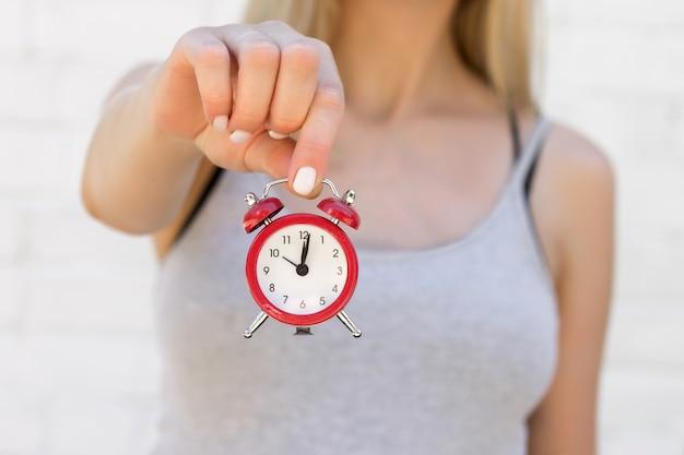 A garota tem um despertador vermelho na mão estendida. tempo, sono, conceito de despertar