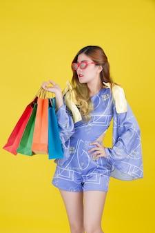 A garota tem um saco de compras de moda e detém um cartão inteligente sobre um fundo amarelo.