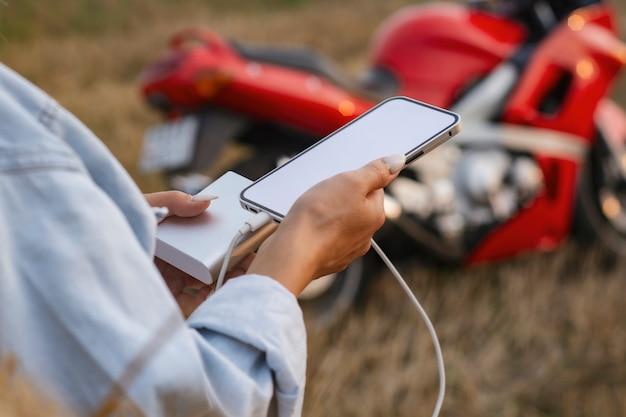 A garota tem um smartphone nas mãos. power bank carrega o telefone tendo como pano de fundo uma motocicleta e a natureza.