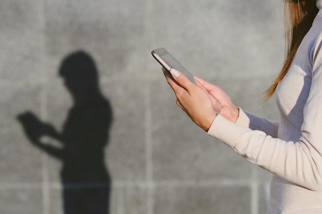 A garota tem um tablet preto nas mãos. contra o fundo de uma parede de concreto cinza, uma silhueta permanece com uma sombra clara.