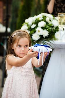 A garota tem um travesseiro com anéis de casamento durante uma cerimônia de casamento
