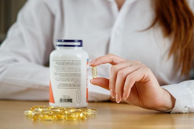 A garota tem uma cápsula de óleo de peixe na mão. cápsulas de omega3 na mesa e na mão do médico.