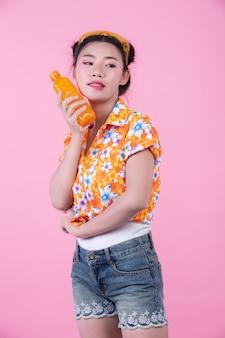 A garota tem uma garrafa de suco de laranja em um fundo rosa.