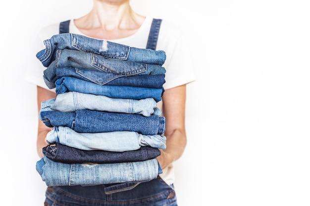 A garota tem uma pilha de jeans nas mãos. limpeza no armário.