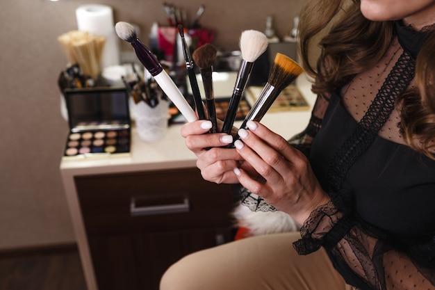 A garota tem vários pincéis de maquiagem nas mãos, close-up.