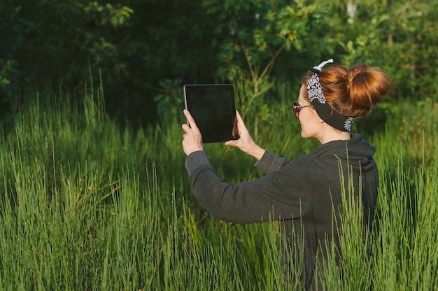 A garota tira fotos do tablet no fundo de uma bela natureza ao ar livre.