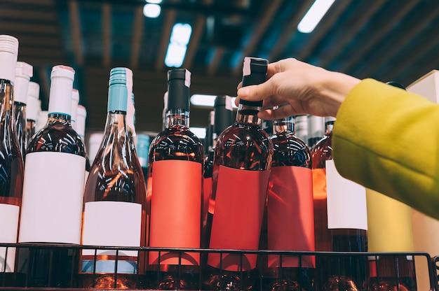 A garota tira uma garrafa de vinho do balcão do supermercado.