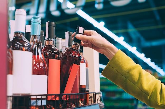 A garota tira uma garrafa de vinho rosé do balcão da loja.