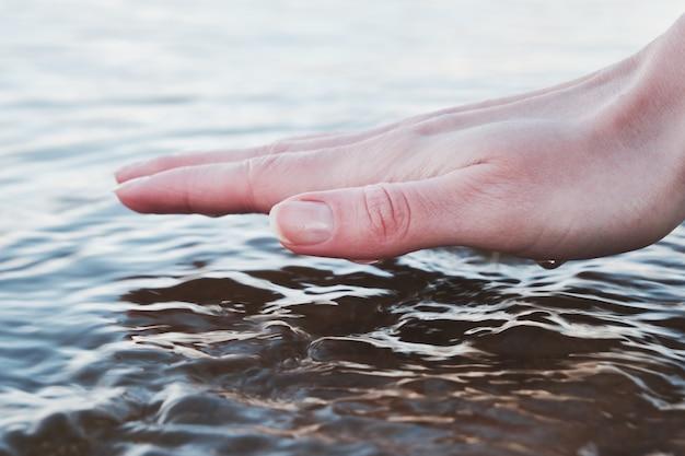 A garota toca a superfície da água. fora da cidade.