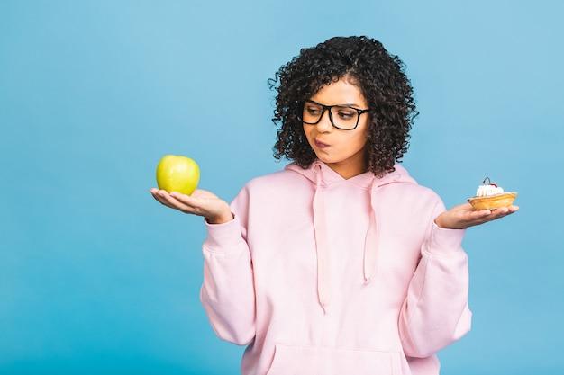 A garota toma a decisão. a garota afro americana não come bolo. conceito de dieta. concepção para perder peso. isolado sobre fundo azul. segurando maçã e bolo.