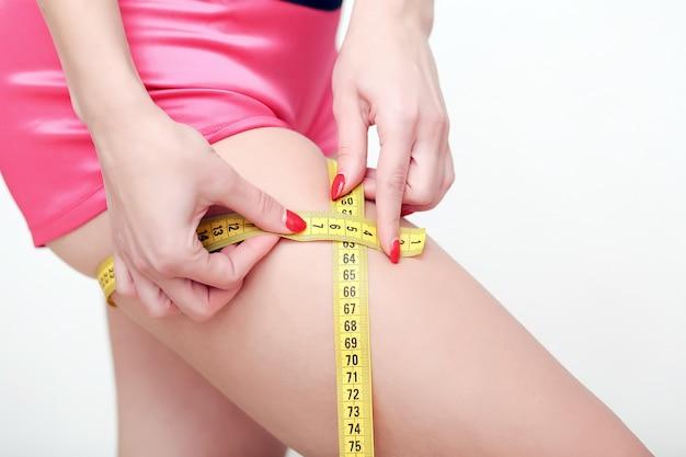 A garota tomando medidas de seu corpo