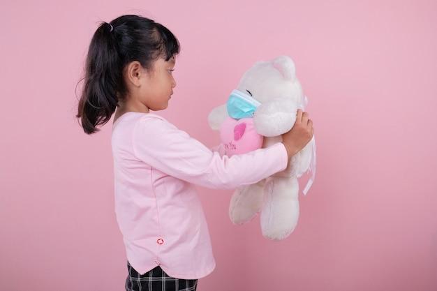 A garota traz o urso usando máscara médica