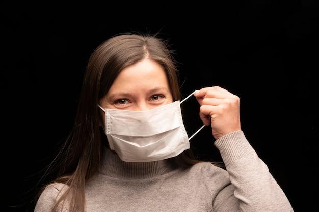 A garota usa uma máscara médica protetora contra vírus e infecções e coronavírus cobiçado em 2019. seus olhos sorriem. retrato do close-up em um fundo preto