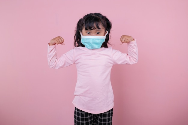 A garota usando uma máscara médica crianças fortes