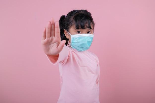 A garota usando uma máscara médica e mostrando o sinal de ok