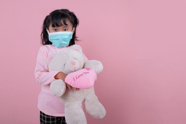 A garota usando uma máscara médica, traga um brinquedo