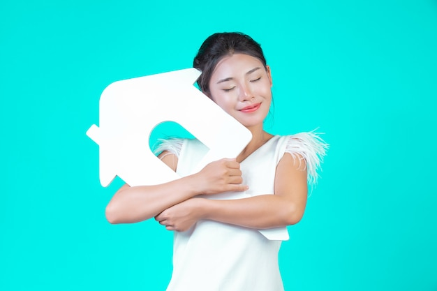 A garota usava uma camisa branca de mangas compridas com padrão floral, segurando o símbolo da casa e mostrando vários gestos com um azul.