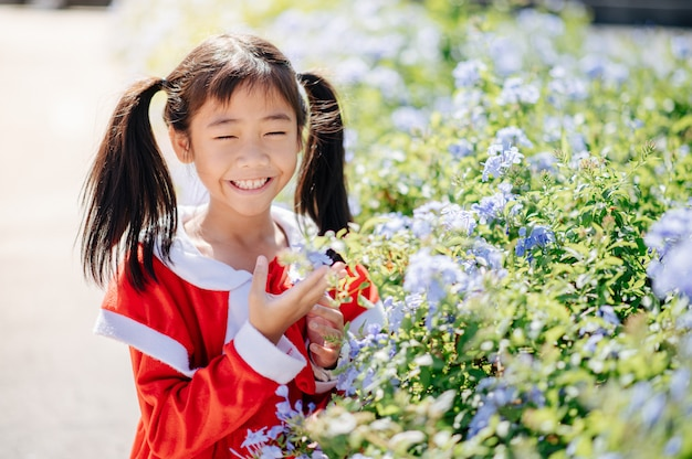 A garota vestindo a roupa de sandy está sorrindo, rindo alegremente. entre as flores