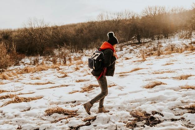 A garota viajante corre ao longo da estrada nevada para as montanhas.