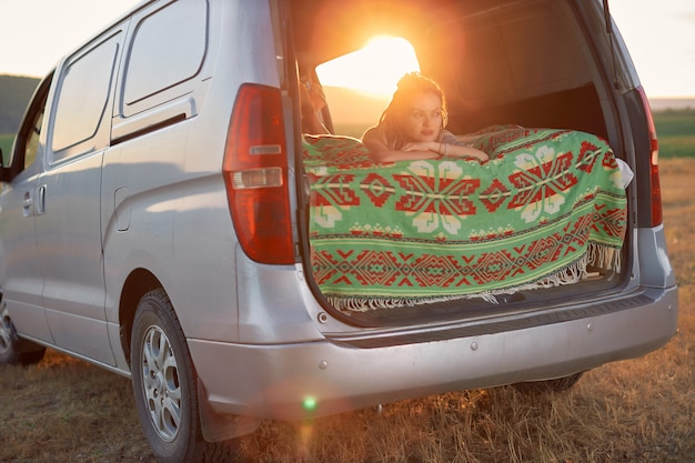 A garota viajante está deitada dentro de uma minivan prateada sobre um cobertor brilhante e olha para a frente contra o bac ...