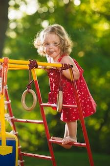 A garotinha brincando no parquinho ao ar livre