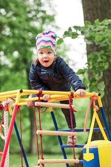 A garotinha brincando no playground ao ar livre