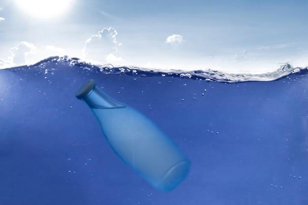 A garrafa de vidro transparente debaixo d'água no oceano