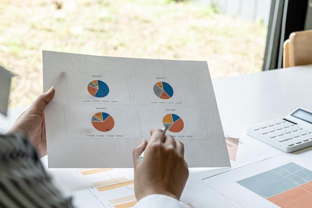 A gerente de vendas aponta para o resumo de vendas, ela verifica as vendas de cada filial, verifica as informações antes de apresentá-las na reunião para a gerência. conceito de gestão de vendas.