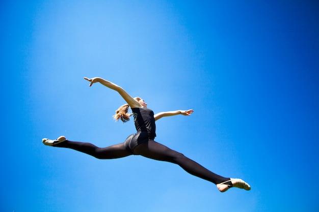 A ginasta nova de sorriso está saltando na separação e flutuando acima da terra.