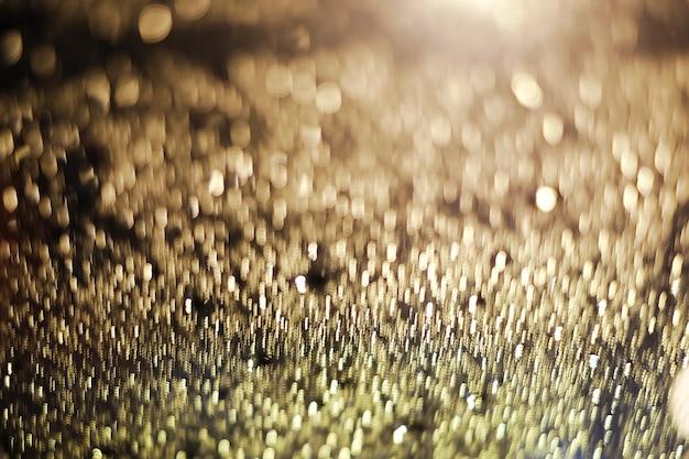 A gota de forma abstrata do bokeh da luz do ouro, a imagem é borrada e filtrada
