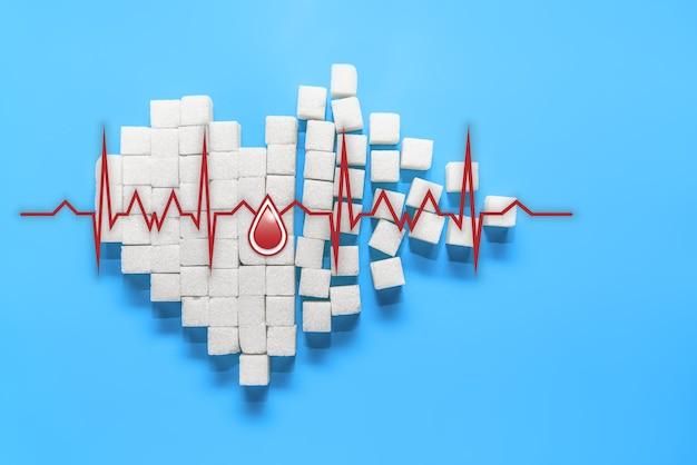 A gota de sangue em um coração partido feito de cubos de açúcar branco puro sobre fundo azul, dia mundial da diabetes