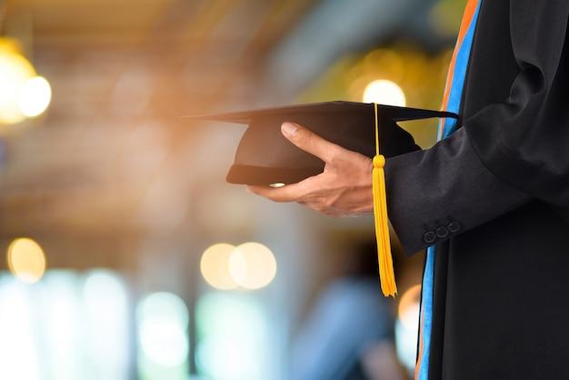 A graduação toma uma borla amarela preta na frente do fundo obscuro do bokeh