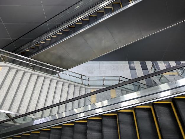 A grande escadaria vazia e a nova escada rolante gêmea estão funcionando no piso da plataforma da estação de metrô, testando a funcionalidade antes do serviço real, vista frontal para o fundo.