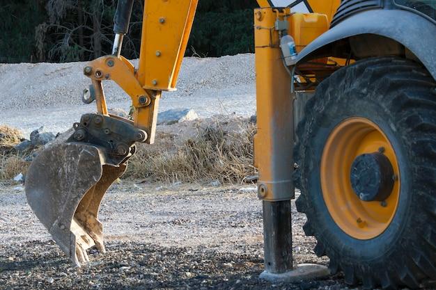 A grande roda amarela de um trator com pneu preto, coberta de lama, pé hidráulico e balde. escavando peças de máquinas, detalhe da indústria de escavadeira. dentes sujos da caçamba de escavadeira de construção