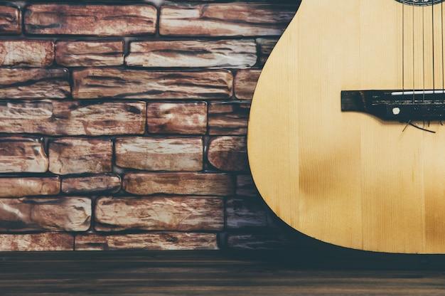 A guitarra acústica está em um fundo da parede de tijolo.
