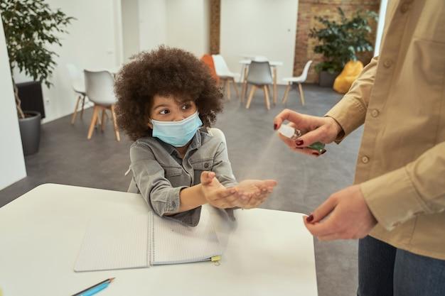 A higiene é importante, adorável garotinho de escola usando máscara protetora pronto para limpar seu