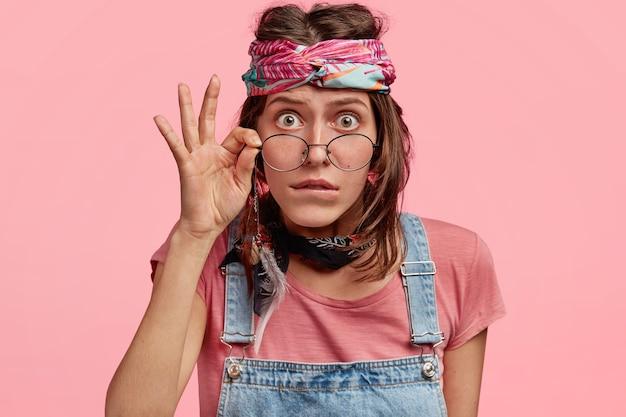 A hippie surpreendida usa bandana e macacão, olha escrupulosamente através dos óculos, lê algo incomum, fica encostada na parede rosa. mulher hippie emocionada e entorpecida em pé