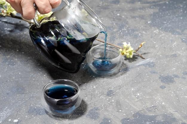 A hora azul é despejada de um bule de vidro em um copo de vidro.