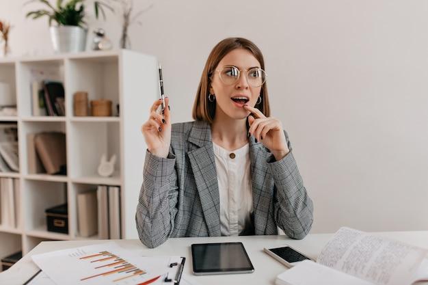 A ideia brilhante veio à mente de uma jovem mulher de negócios em uma jaqueta elegante e óculos, sentada no local de trabalho.
