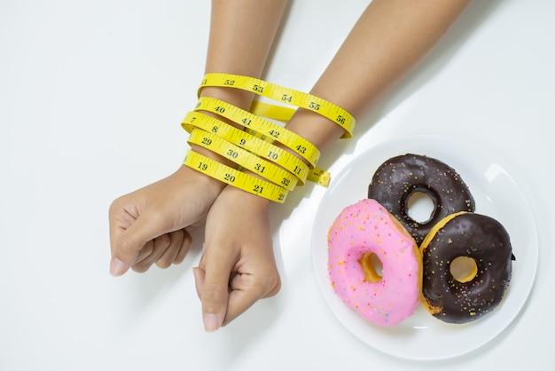 A ideia superior de duas mãos da jovem mulher foi amarrada medindo a fita.
