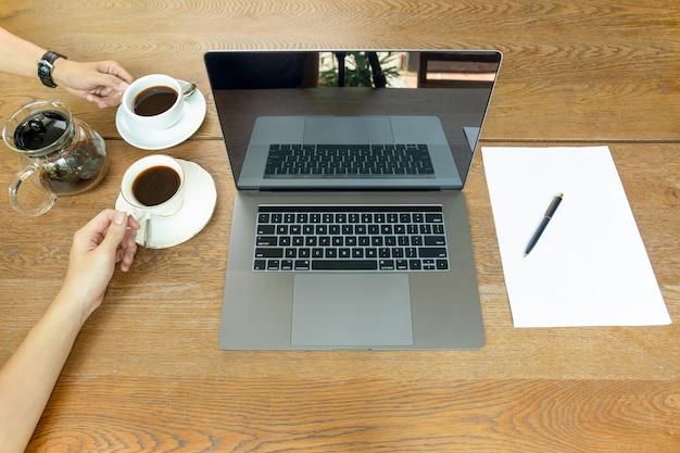 A ideia superior do homem de negócios entrega guardar o copo de café com o portátil na tabela.
