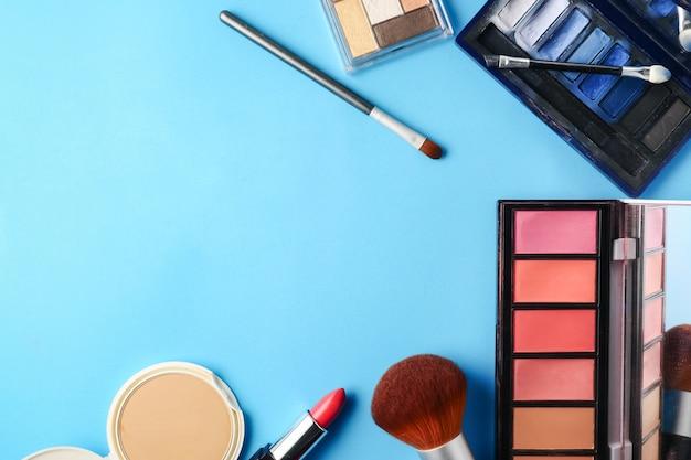 A ideia superior dos cosméticos ajustou-se para a composição em um fundo azul. espaço livre para o texto.