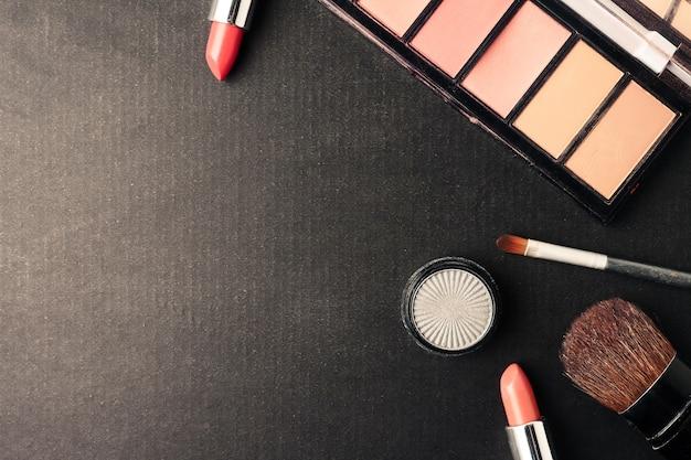 A ideia superior dos cosméticos ajustou-se para a composição em um fundo preto. espaço livre para o texto.