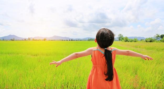 A ideia traseira dos braços asiáticos pequenos do estiramento da menina da criança e relaxou nos campos de almofada verdes novos com luz solar da manhã.